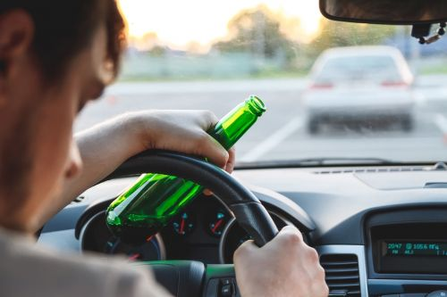 A man driving a car with a beer bottle